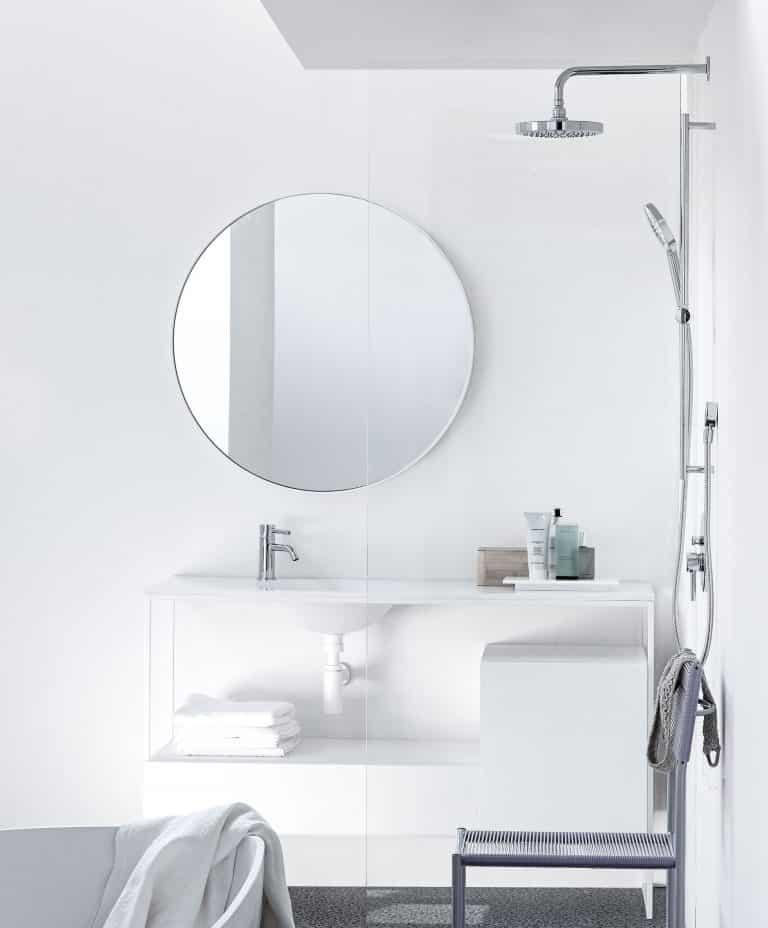 Sprchová souprava na tyči v bílé koupelně s kulatým zrcadlem