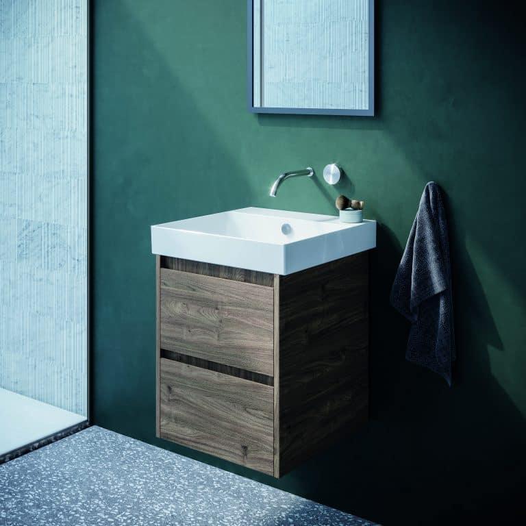Zelená stěrka v koupelně, tmavá dřevěná skříňka pod umyvadlo se dvěmi zásuvkam, baterie ze zdii