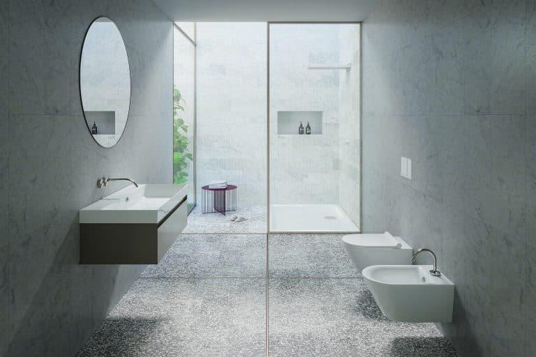 Šedá koupelna se srpchovým koutem, wc a bidet, umyvadlo na zdi s dřevěnou skříňkou, kulaté zrcadlo