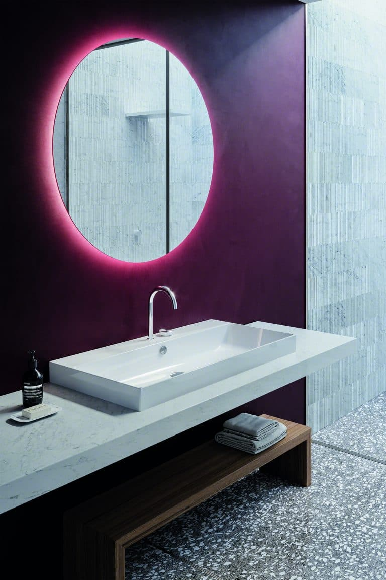 Umyvadlo na desce z kamene, dřevěná lavice, fialová stěna, kulaté zrcadlo