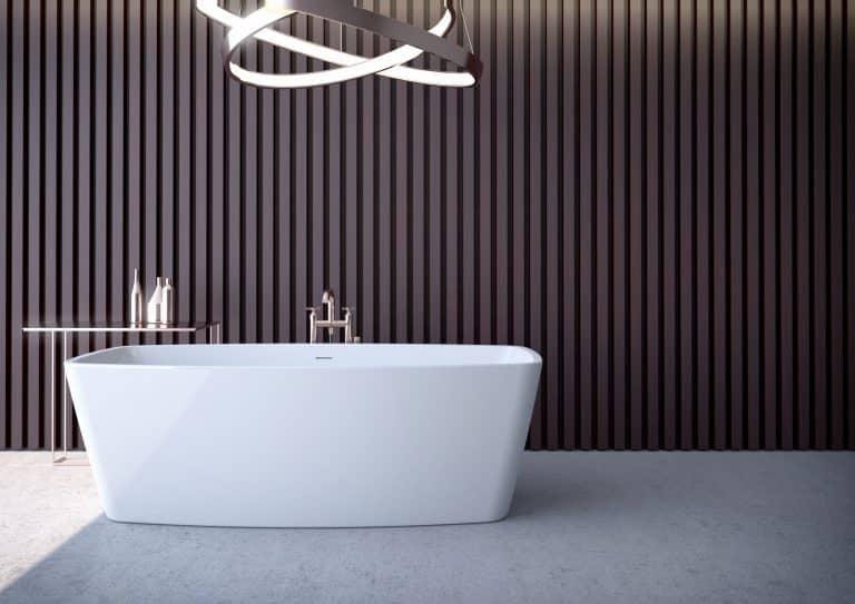 Koupelna s černým obkladem, vana do prostoru s kovovým odkládacím stolkem a baterií z podlahy