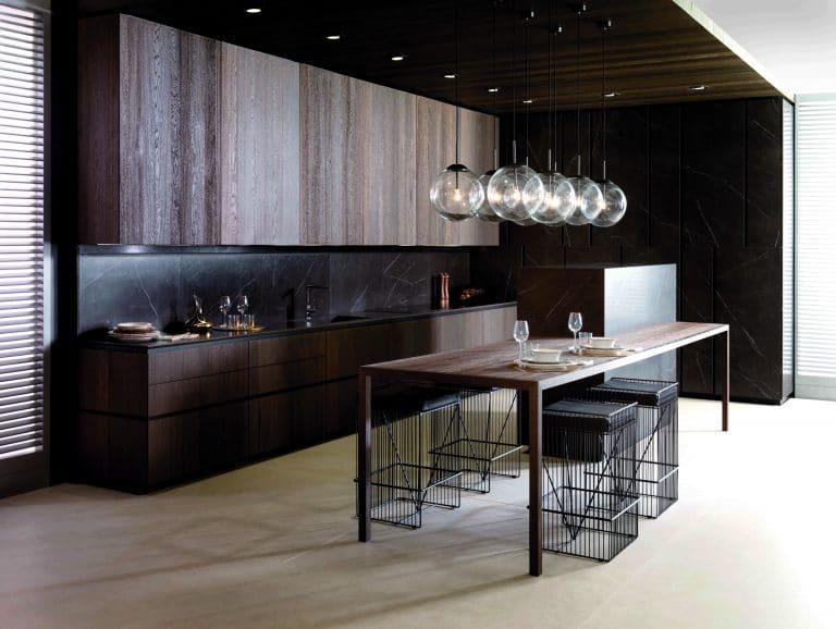 tmavá kuchyně ve dřevě, kulaté lustry, ostrůvek s kovovými barovými židlemi