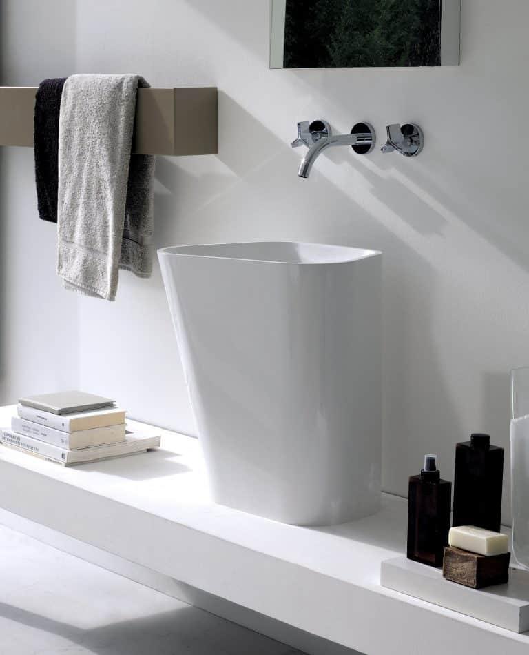 vysoké umyvadlo na desce z umělého kamene, černé doplňky, knihy v koupelně, držák na ručník