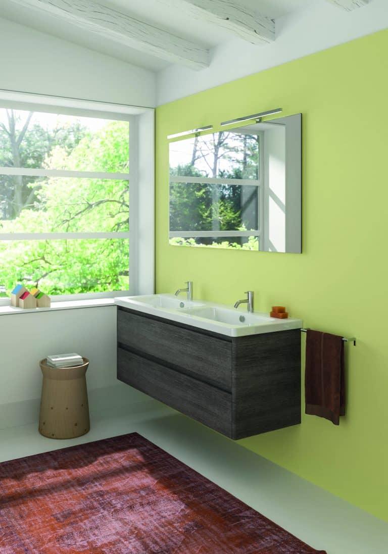 Koupelna se zelenou stěrkou na zdi, dvojumyvadlo s dřevěnou skříňkou, červený koberec