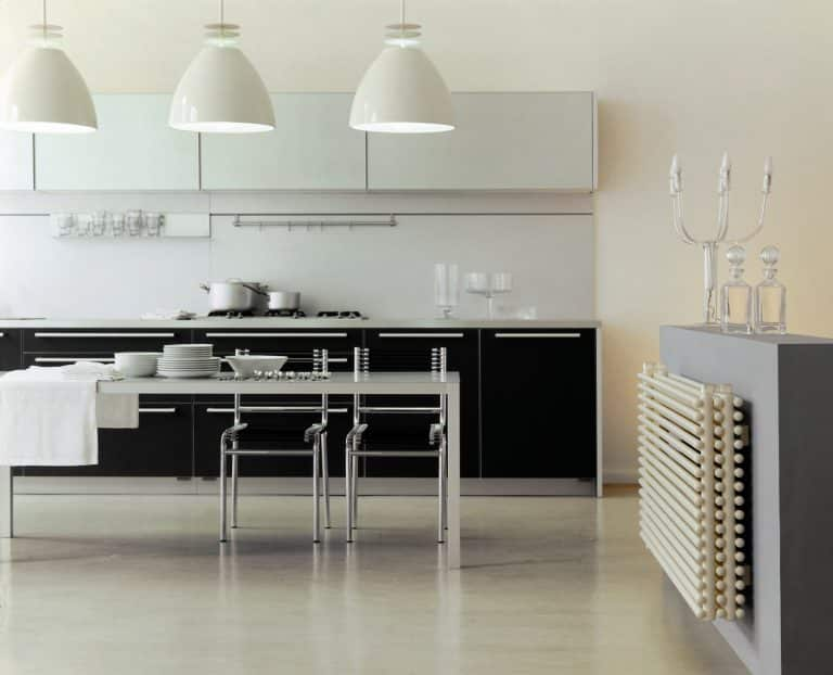 Kuchyň s kuchyňským stolem, bílé lustry, trubkový bílý radiátor na zdi