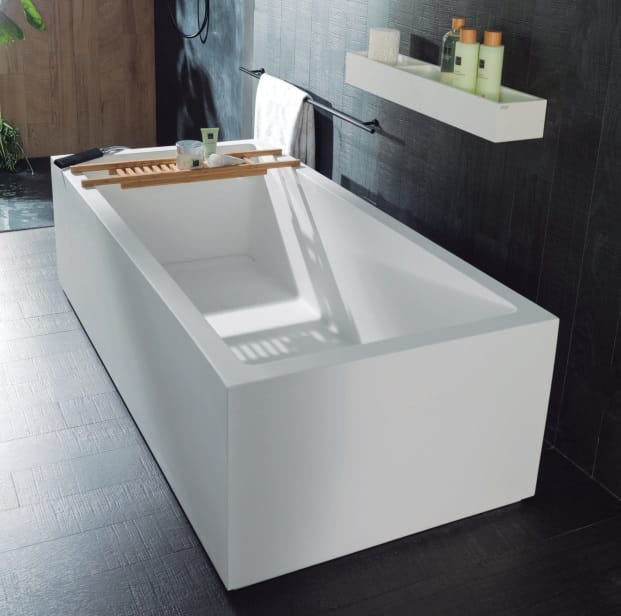 Černá koupelna s hranatou vanou do prostoru, dřevěná odkládací přenosná polička na vanu, černý obklad a černá dlažba