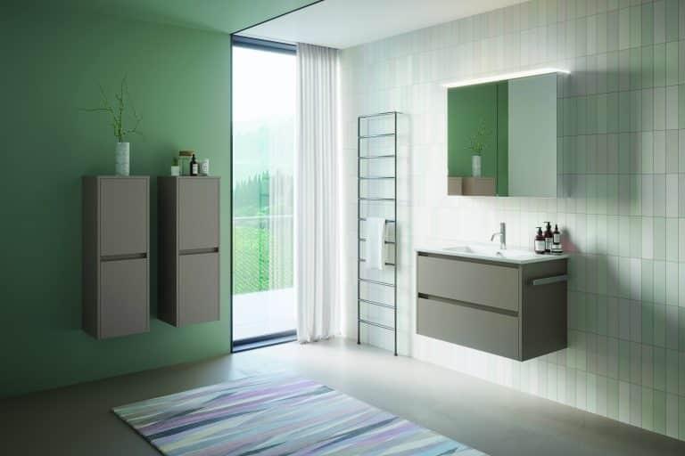 Koupelna se zelenou stěnou, barevný koberec, dřevěná umyvadlová skříňka s držákem na ručník