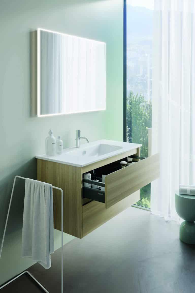 Koupelna s výhledem do přírody, zelená stěrka na zdi, dřevěná umyvadlová skříňka s vysunutou zásuvkou