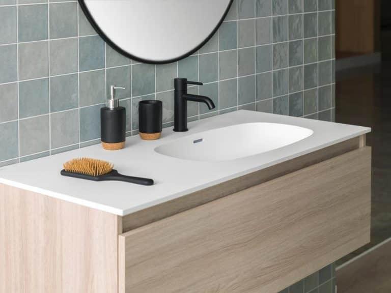 Umyvadlo integrované v desce z umělého kamene, skříňka ze světlého dřeva, kulaté zrcadlo, černá baterie, kalíšek a dávkovač na mýdlo, kartáč