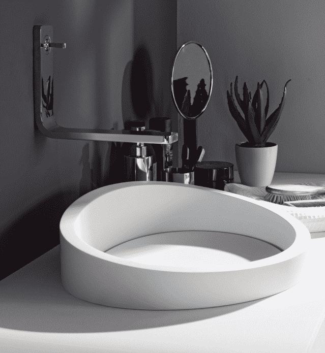 Atypické umyvadlo z umělého kamene na desku, chromová baterie, květina v koupelně