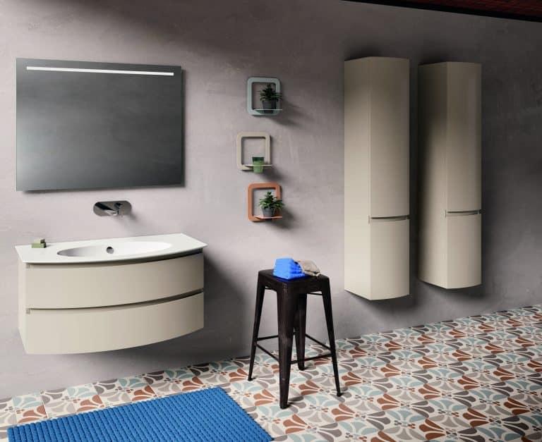 Koupelna v teplých barvách s barevnou dlažbou, béžové skříňky, černá stolička