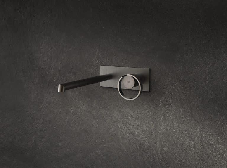 černá umyvadlová podomítková baterie na zdi s obkladem z černého kamene