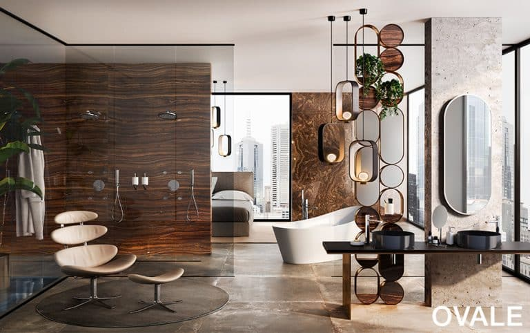 Koupelna s tmavě hnědým mramorem na zdi a podlaze, kožené béžové křeslo, kovová černá umyvadla na desce, oválné zrcadlo, vana do prostoru, sprchové baterie Ovale