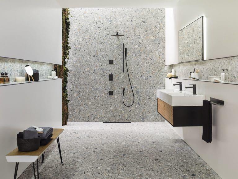 Koupelna se sprchovým koutem s černými bateriemi a černou sprchou, šedá dlažba a obklad s imitací kamene, dřevěná lavice, živá stěna