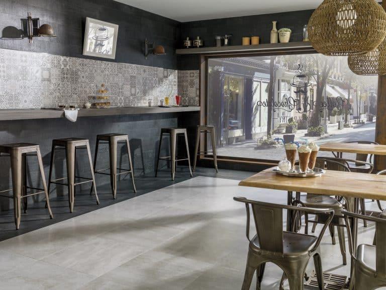 Kavárna s betonovou dlažbou, barem a kovovými barovými židlemi, retro obkladem s ornamenty, proutěné lustry