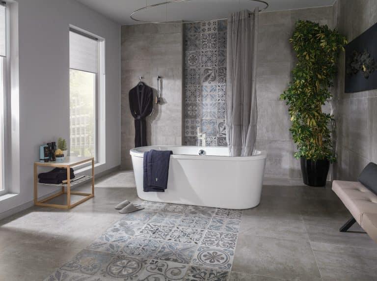 šedá betonová koupelna s kombinovanou dlažbou a obkladem retro dekoru, vana do prostoru, velká květina, závěs u vany