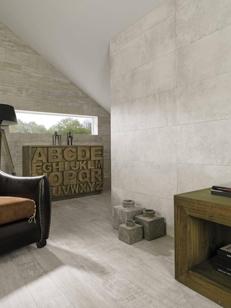 Pracovna s šedým obkladem imitujícím beton, betonové vázy, kožené křeslo