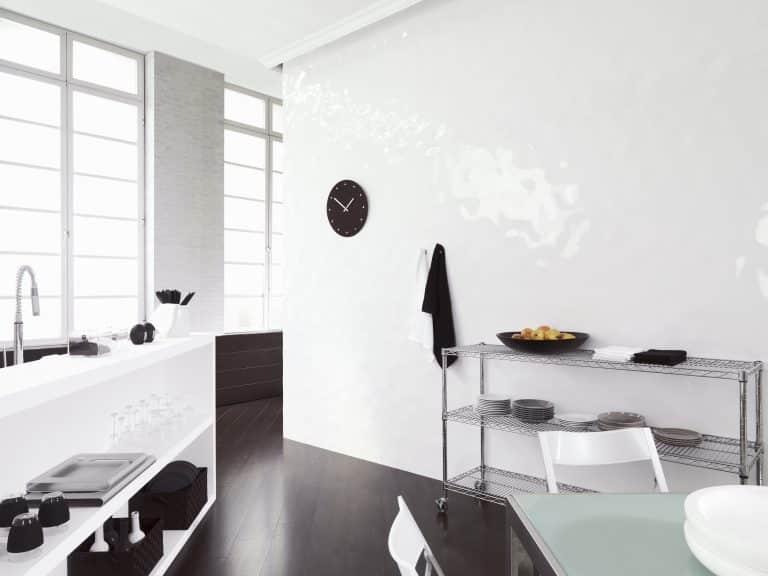 bílá kuchyně s bílým lesklým obkladem a černou dřevěnou podlahou