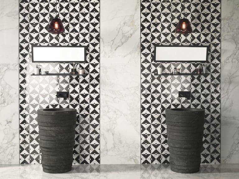 Koupelna s černobílým obkladem a mramorem, černá kamenná umyvadla na postavení, měděné lustry