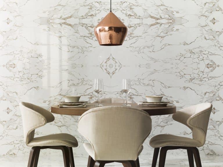 jídelna s mramorovým bílým obkladem, bronzový lustr, kulatý stolek s béžovými polstrovanými židlemi