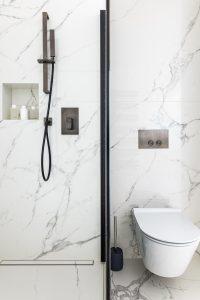Bílý mramorový sprchový kout, skleněná zástěna, závěsná toaleta, černá sprchová souprava na tyči