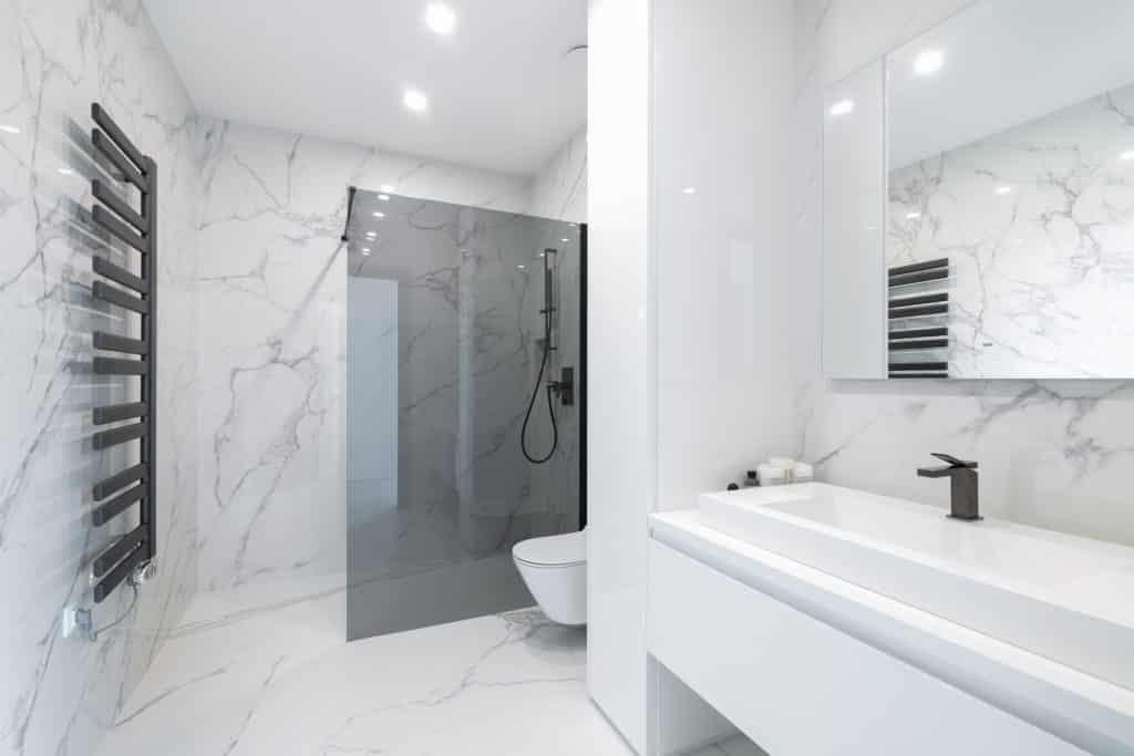 Bílá mramorová koupelna, sprchová zástěna typu walk-in, toaleta závěsná, černá sprchová souprava na tyči