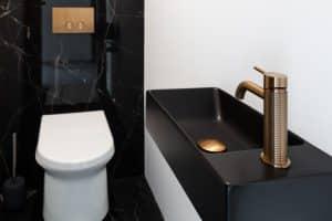 toaleta s černým mramorovým obkladem, černé umyvadlo se zlatou umyvadlovoubaterií
