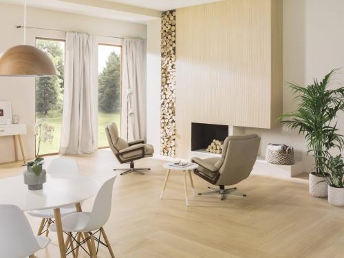 Obývací pokoj s krbem obloženým dřevěným obkladem, zásobník na dřevo, světlá dřevěná podlaha, bílý stůl a židle