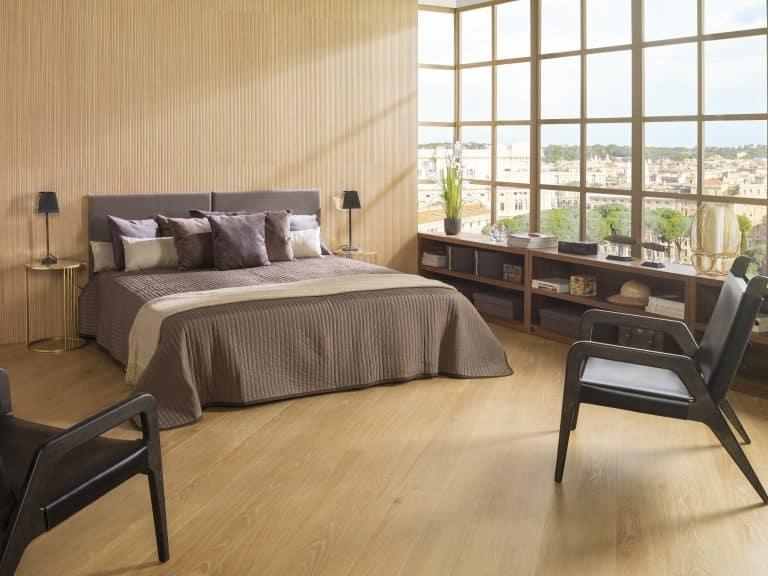 Ložnice s obkladem dřeva a dřevěnou podlahou, prosklená stěna, hnědá postel, hnědá křesla