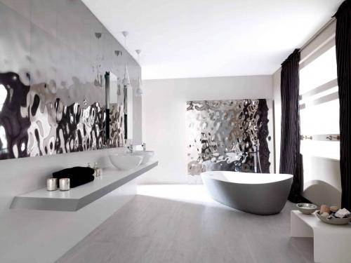 Koupelna se stříbrným obkladem, umyvadla na desce, šedá volně stojící vana, černé závěsy v koupelně