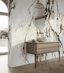 hnědá umyvadlová skříňka, mramorová zeď, kulaté zrcadlo