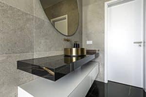 luxusní koupelna se zlatým kovovým umyvadlem na černé desce, bílá skříňka, černá mramorová podlaha, kulaté zrcadlo, betonový obklad