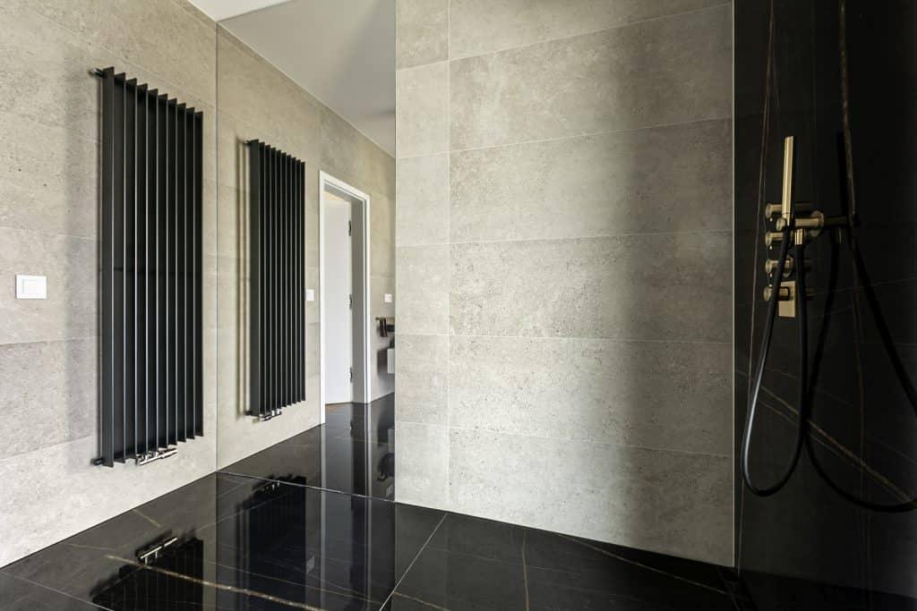 Černá mramorová koupelna s velkoformátovým obkladem a dlažbou, černé radiátory, betonový obklad na zdi, zlatá sprchová baterie
