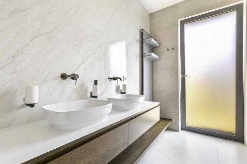 Bílá mramorová koupelna s velkoformátovým obkladem a dlažbou, oválná umyvadla na desce z umělého kamene, radiátor s poličkami na ručníky
