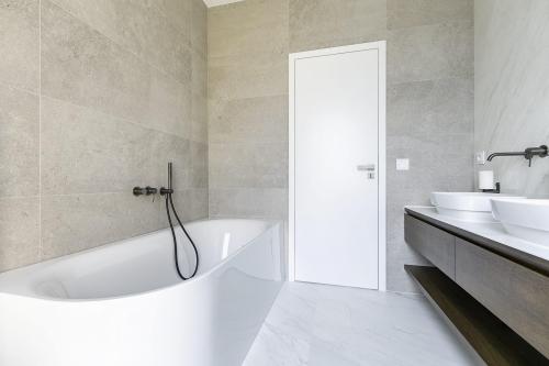 Koupelna s bílým mramorem na podlaze, bílá oválná umyvadla na desce z umělého kamene, dřevěná skříňka pod umyvadlo, rohová vana, černá vanová baterie, betonový obklad