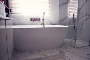 Koupelna s mramorovým obkladem a dlažbou, designová vana do prostoru, měděná vodovodní vanová baterie na zdi, skledněný sprchový kout, skříňka pod umyvadlo