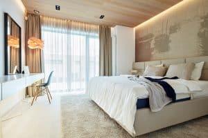 Ložnice v teplých barvách, koberec v ložnici, designové osvětlení, tapeta moře a lodí