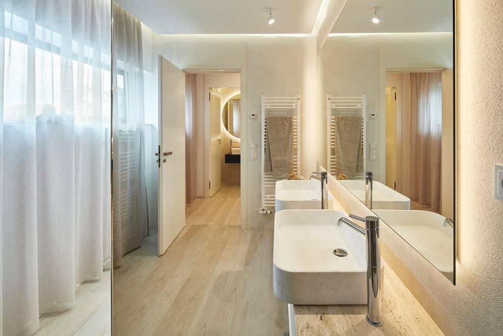 Koupelna s dlažbou v dekoru dřeva, mramorová deska pod umyvadlem, umyvadla na desce, bílý radiátor
