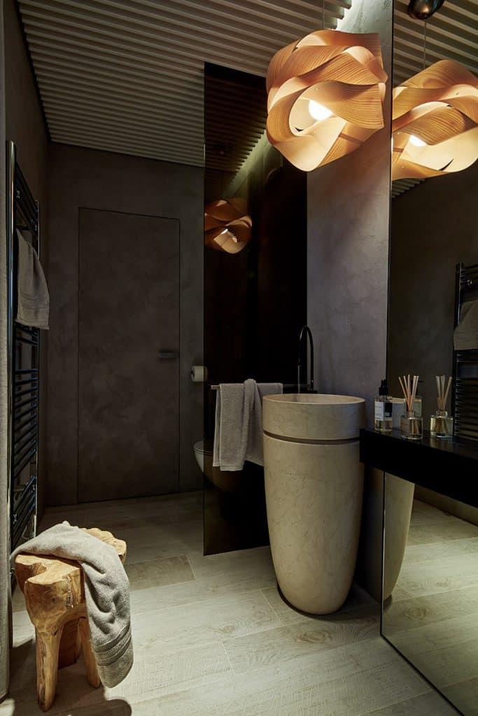 Koupelna s toaletou, kamenné umyvadlo na postavení, designové osvětlení