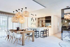 Bílá kuchyně s ostrůvkem, designové osvětlení v kuchyni, jídelní stůl z masivu